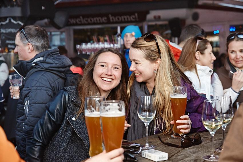 Zwei Damen genießen Bier in einem Après Ski Lokal in St. Anton am Arlberg