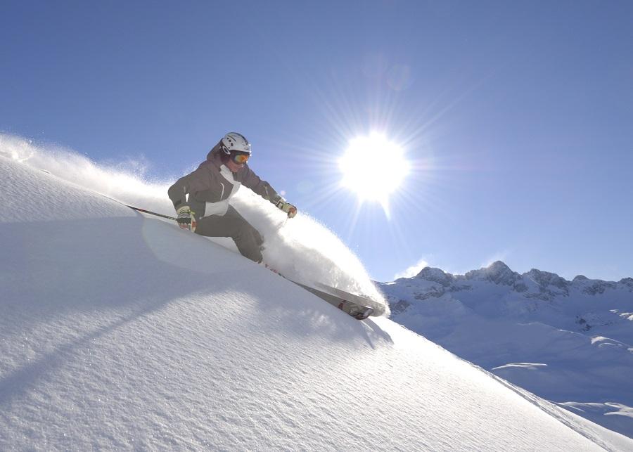 Skifahrerin unterwegs auf der Piste am Arlberg an einem sonnigen Wintertag