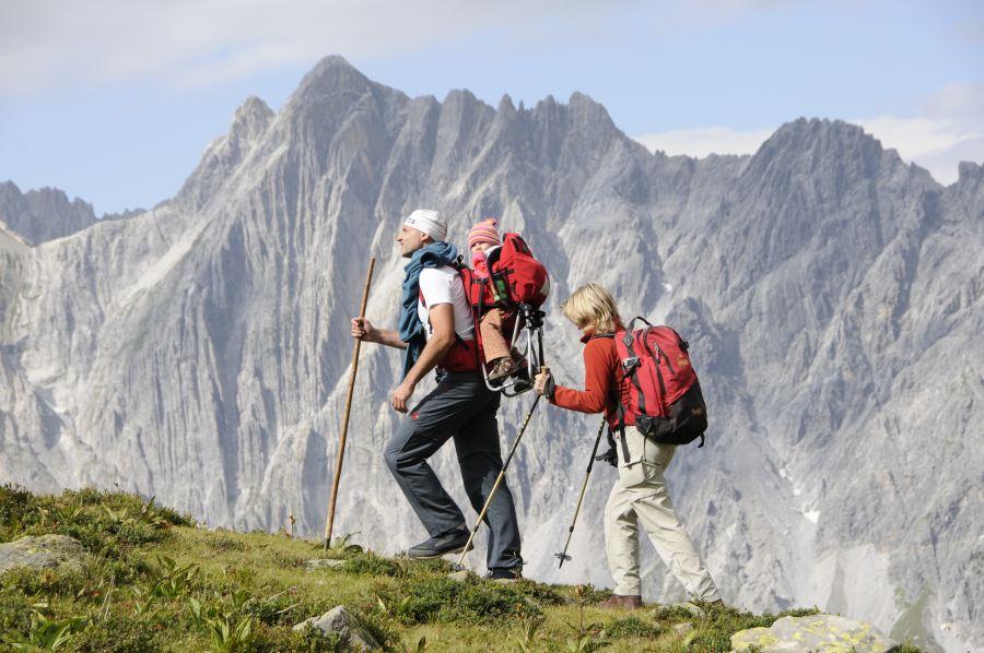 Pärchen wandert mit dem Baby im Rücksack in der Höhenluft am Arlberg